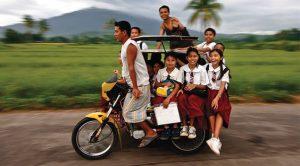 トライシクルに乗って家に帰る女子学生たち