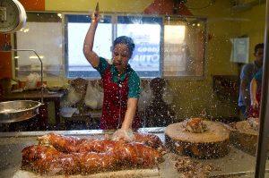 出刃包丁で豪快に豚を叩き割る女性スタッフ