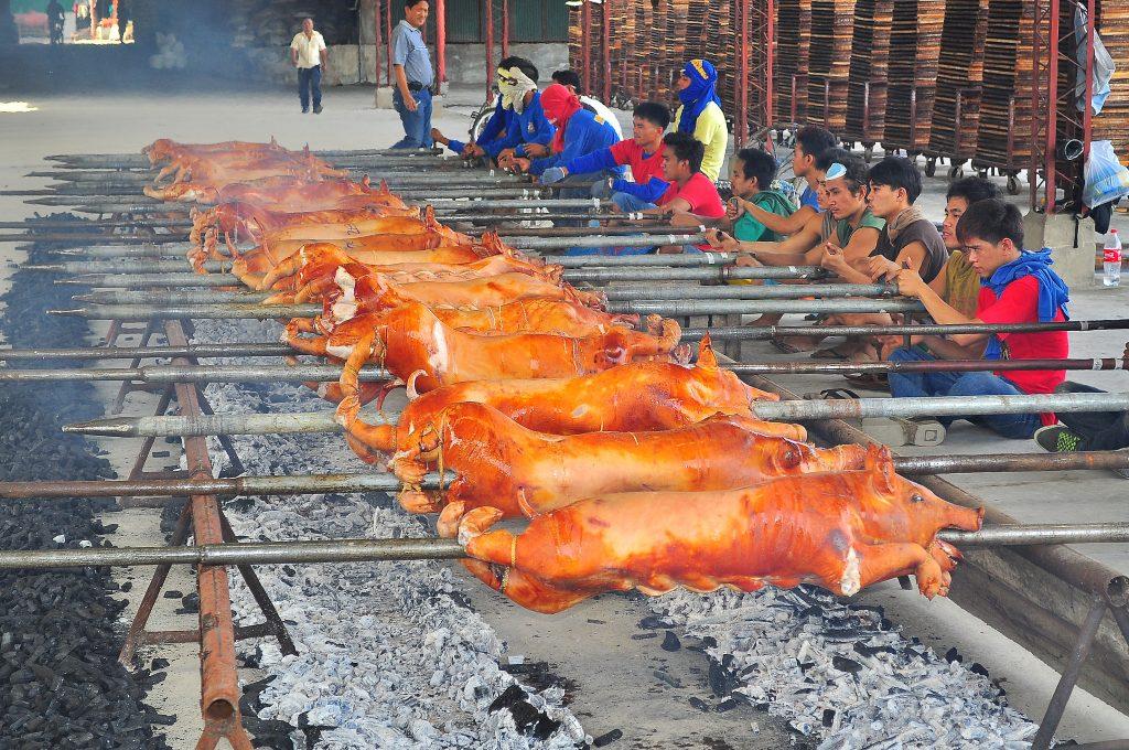炭火でまるごと焼かれている豚