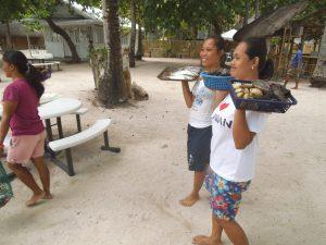 海鮮物を皿に持って売り歩くパンダン島の女性達