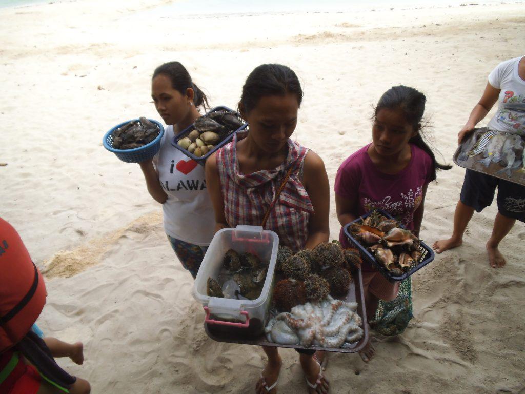 生きた海の幸を料理用に売り歩く島の女性たち