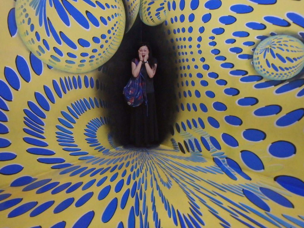 カラフルな模様の中心の暗点から一般客が顔をだしているように見えるトリックアート