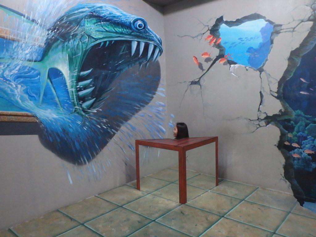 怪獣が一般客の頭部を食べようとしているように見えるトリックアート