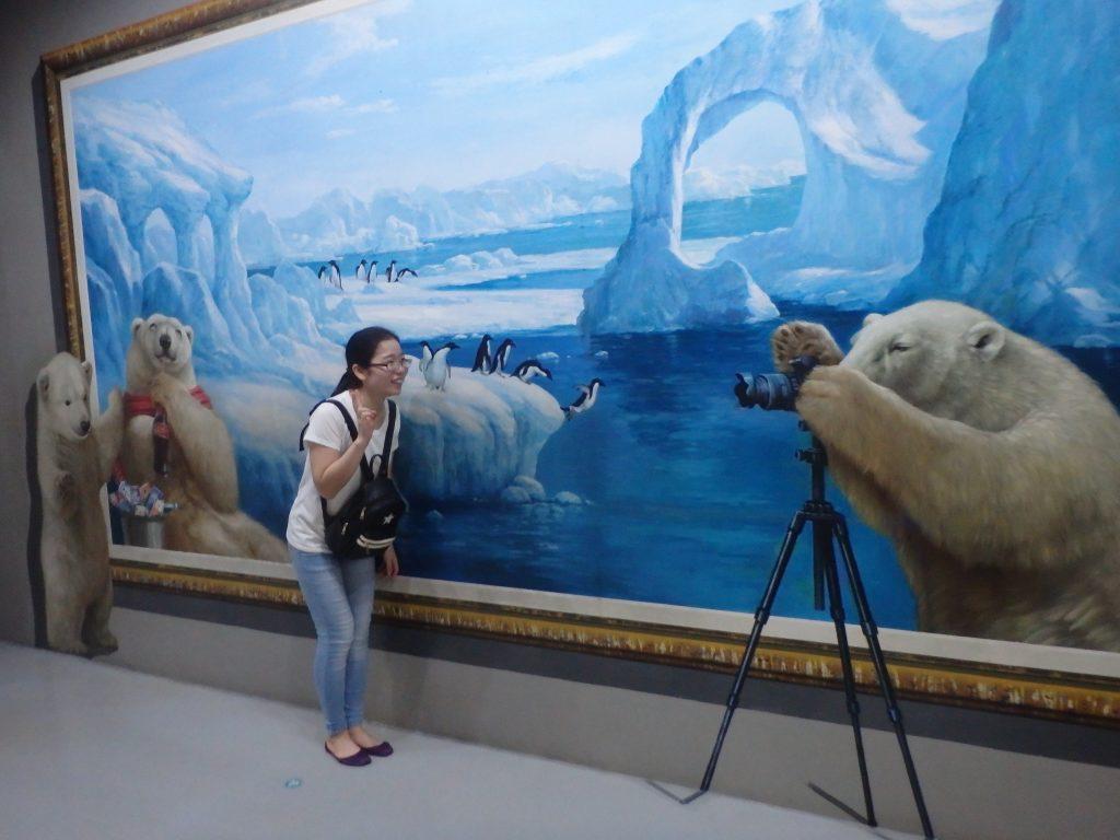 お母さんクマが小熊と一般客にカメラで写真を撮っているように見えるトリックアート