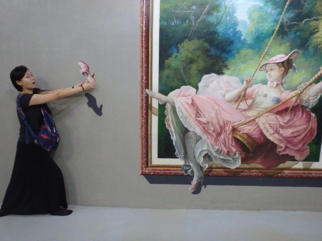 貴婦人の飛び散った片足の靴をダイレクトキャッチする一般客のトリックアート