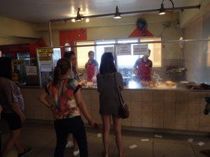 店内のガラス張り厨房の中で作業するスタッフたち