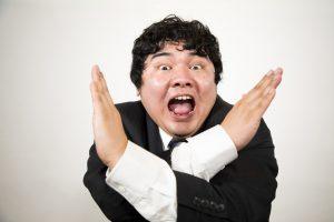 両腕でバッテンじるしを作り拒絶反応を示す日本人