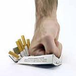 こぶしでタバコの箱をつぶしている
