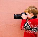 なにかを見つけた子供が一眼レフで写真を撮っている