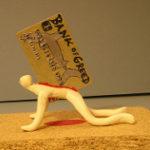 大きなクレジットカードを背中に背負いこみ負担を感じている人形
