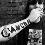 火のついたタバコを持っている右腕にCancerというにせの刺青が書かれています