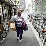 手提げかばんやリュックなどたくさんの荷物を背負う大阪のおばさん
