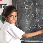 黒板にアルファベットを綴る小さな女の子