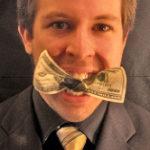 ドル紙幣を口にくわえるアメリカ人