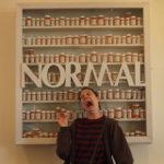 ノーマルという文字看板の前でアブノーマルな表情を見せる女性