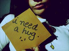 I need your hugと書かれたボードを持つ女性