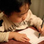 左手で手紙を書く子供