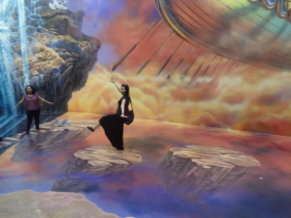 岩の踏み台をジャンプして渡る女性
