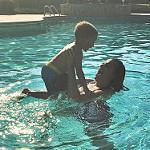 息子とプールで遊ぶお母さん