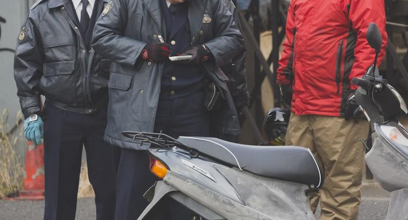 不審なバイク運転手に事情聴衆する警察官