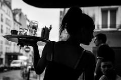 トレイで飲み物を運ぶカフェの女性
