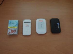 過去に利用したポケットWifi3台とメビウスというタバコを並べて大きさを比較した写真