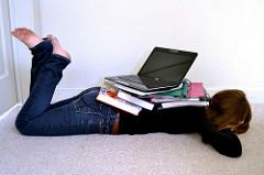 ノートPCとテキストの下敷きになっている女性