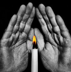 ロウソクに両手をかざして暖を取っている。