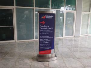 ターミナル2の無料シャトルバスの乗り場を⇒で示す案内標識