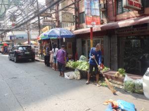 お店の周りをほうきで掃除する露天野菜行商