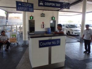 クーポンタクシーの受付デスク。右には白いタクシーが並んでいます。デスクの上の看板にはCoupon Taxiと書かれています。