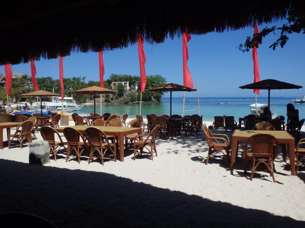 白浜の上に屋根付きテーブルと椅子が並べられたマラパスクア島のレストラン