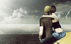 渚で海を眺めるカップル