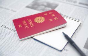 英字新聞の上に置かれた日本国パスポート