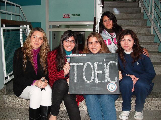 TOEICと書かれた黒板ボードを掲げる女学生たち