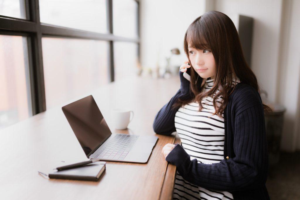 机の前に座っている学生風の女性