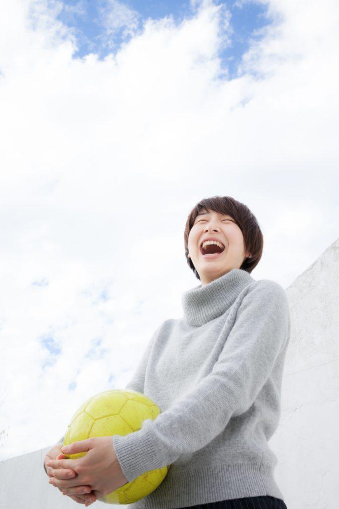 サッカーボールを持ち、大声をあげる活発な女性