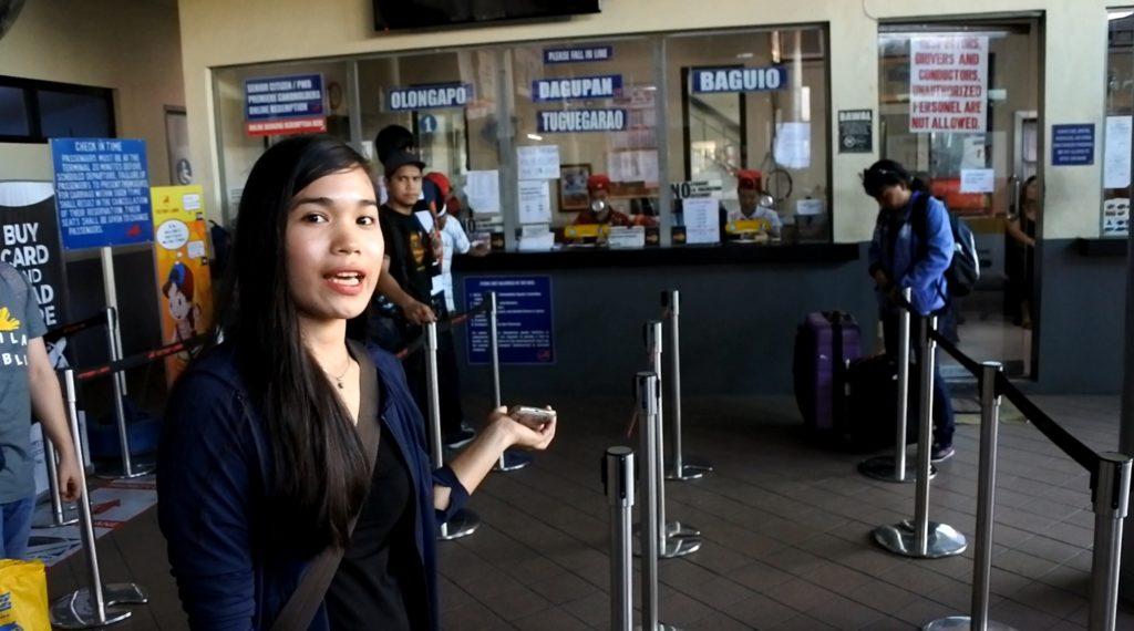 ビクトリーライナーバスターミナルのチケット売り場を案内するジェニー