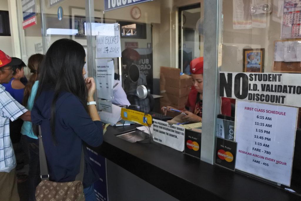 売り場でバスチケットを購入する家政婦ジェニー