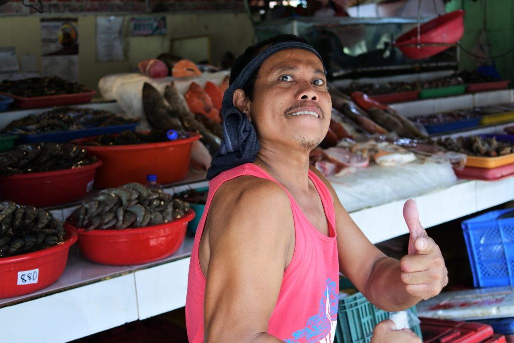 ポーズを決めるマッチョな魚屋おじさん