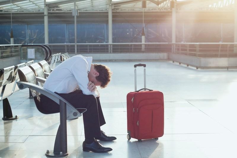 欠航か遅延かなにかで空港の椅子で眠り込んでいる男性