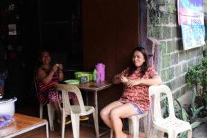 Irene's Empanadaの店先に座る店員二人