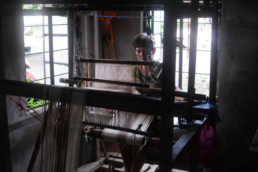 手作業で織物を縫うおばあさん
