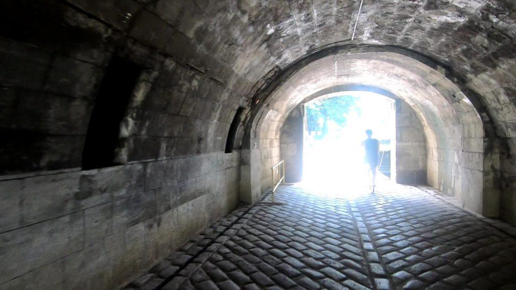 自転車で石造りのトンネルを駆け抜ける