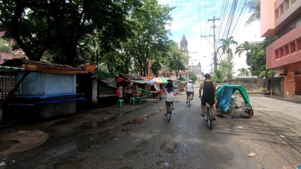 自転車でマニラ大聖堂の近くを駆け抜けるツアーグループ