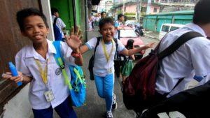市場の前で手を振る子供達