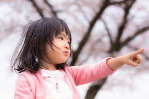 遠くを指さす小さな女の子