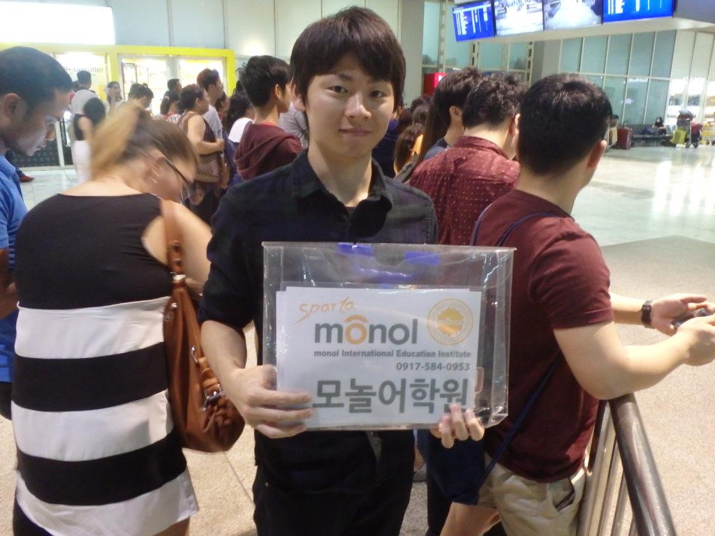 MONOLという語学学校のボードを掲げるピックアップ担当者