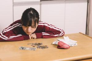 机の上で小銭を数える若い女性