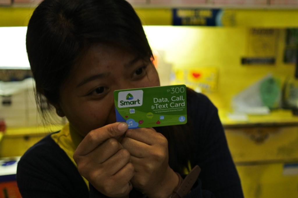 300ペソのプリペイドカードを手にもつ女性